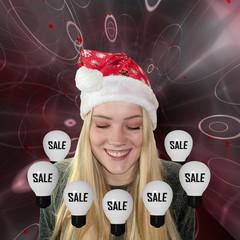 lachendes, Junges Mädchen mit langen blonden Haaren und Weihnachtsmütze schaut auf Glühbirnen mit Sale.