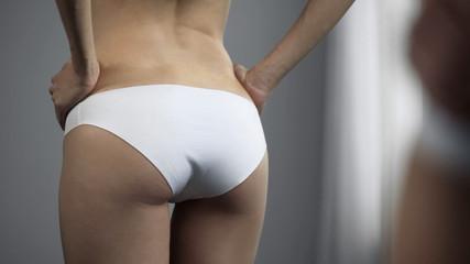 Slim female in white underwear standing in front of mirror, body shape, closeup