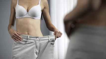 Athletic woman in white bra wearing plus size jeans, diet and weight loss