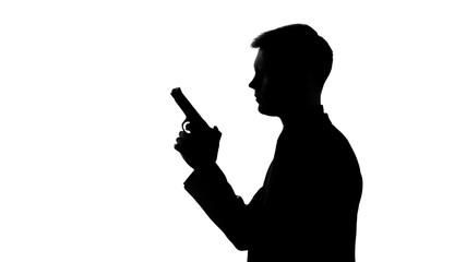 Male silhouette holding gun, preparing to shoot, revenge, contract killing