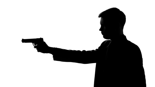 Man in suit pointing gun, threatening with weapon, revenge, silhouette side view