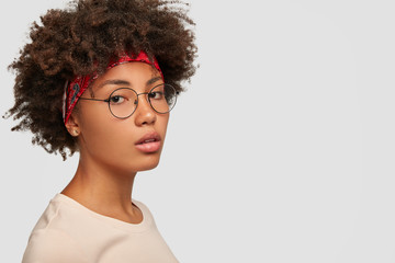 Pretty charming lady stands sideways, looks with serious expression, wears round glasses, red headband, has self confident look, models against white background with free space for your information