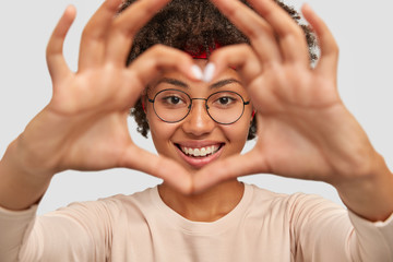 Photo of attractive young woman makes heart shape gesture over face, smiles broadly, demonstrates her love to boyfriend, wears round spectacles, isolated over white background, gestures indoor