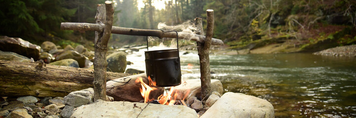 Cooking food in pot over campfire outdoor