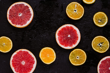 Delicious various types fresh cut of citrus fruit  on dark background.  Healthy eating, dieting.