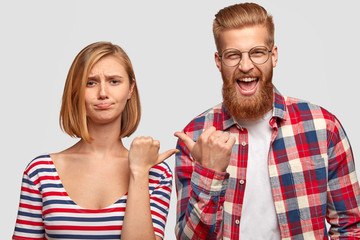 Displeased woman with short hair, frowns face, indicates at ginger guy who smile gladfully, stand closely against white background. Girlfriend and boyfriend point at each other with different emotions
