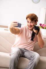 Young man playing with kitten at home