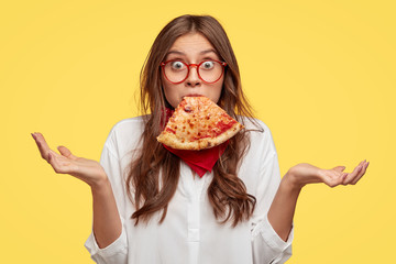 Surprised Caucasian woman keeps slice of pizza in mouth, spreads hands with hesitation, has puzzled facial expression, dressed in white shirt, eats junk food, models against yellow background