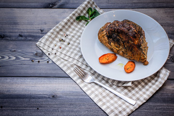 A large piece of baked meat Still life on a light wooden table.