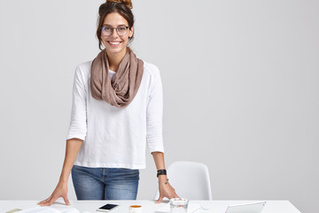 Shot of attractive successful lady or teacher prepares for studying seminar, searches information on modern gadgets, keeps hands at table, wears stylish clothes and spectacles, isolated on white wall