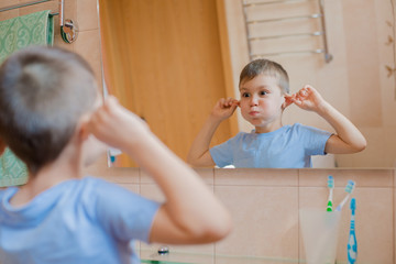 The child grimaces before the mirror in the bathroom. A little boy shows his tongue and has fun.