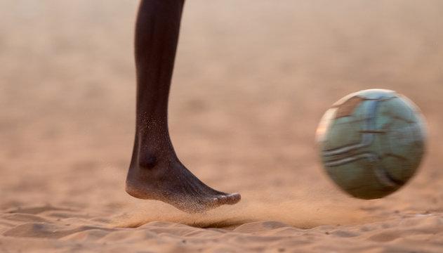 Kids playing football barefoot on sand