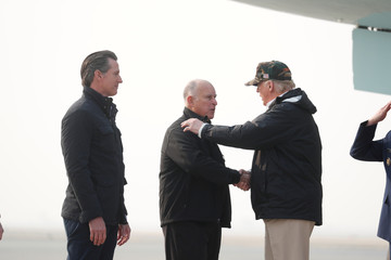 President Donald Trump shakes hands with Governor Jerry Brown as Governor-elect Gavin Newsom looks on upon arriving at Beale Air Force Base California