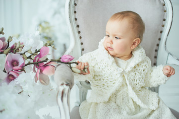 Adorable Ten month old toddler baby girl sitting on chair.
