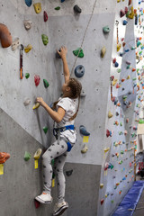 Rock climbing in indoor gym, girl has mountaineering exercises