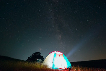 Tourist tent and car at night on the background of the milky way and the starry sky .