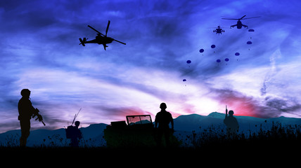 Silhouette of soldiers at night watching the launch of paratroopers