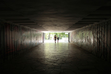 Silhouette of a man with a child in a dark tunnel, view from afar