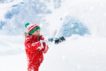 Child brushing off car. Kid with winter snow brush