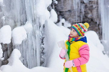 Children play with icicle in snow. Kids winter fun