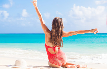 back view of long haired girl in red swimsuit and straw hat on tropical caribbean beach