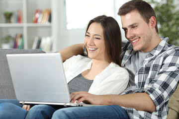 Couple checking online content in a laptop sitting at home