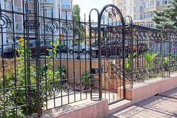 black steel doors and wrought-iron fence with a wrought pattern