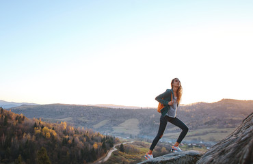 woman hiker with backpack walking on edge of cliff against background of mountains and sunrise.