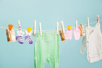 Future costs of having a baby concept. Cute baby clothes hanging on a clothes string.