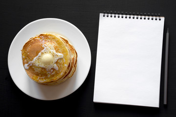 Stack of homemade pancakes with butter on white plate, blank notepad with pencil over black background, overhead view. Space for text.