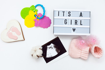 "top view of children's accessories: toys, pacifier, baby screen, baby projector lamp ""it's a girl"", a cotton flower and delicious gingerbread. flat lay pregnancy composition"