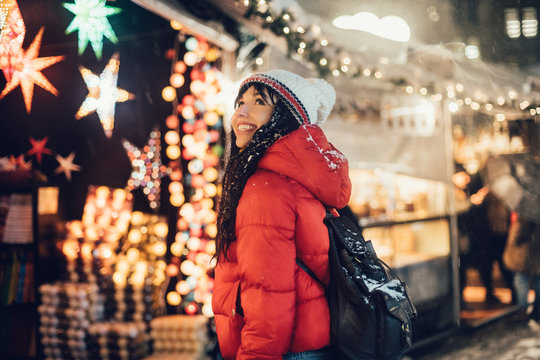 Beautiful happy woman looking for a present on Christmas city fair during snow storm