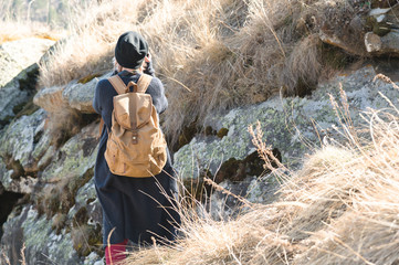 Back view of an attractive female tourist, standing in a hat with a backpack on her shoulders enjoying a sunny afternoon in the mountains. The concept of lifestyle travel