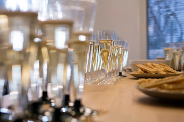 Glasses with champagne and some snacks on a long table at a corporate event.