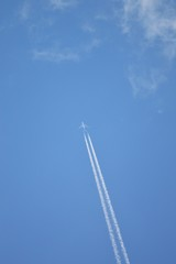 Jet airplane flying the blue sky / trace of the plane in the sky bright day