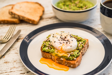 Food photography of an avocado toast with poached egg, sesame seeds, and black coffee. Breakfast, lunch, brunch, light dinner dish meal, vegetarian food, healthy eating concept.