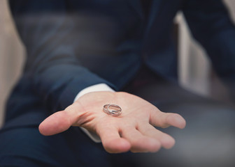 man holding wedding rings in his hand