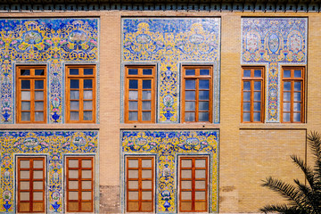 Exterior colorful tilework art on the wall with windows at the Golestan palace. Tehran, Iran