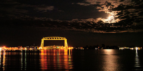 Full moon is seen in clouds over the iconic Duluth Minnesota aerial lift bridge with reflections on calm harbor waters