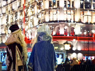 Santa Claus or Father Frost and Snow Maiden on the background of the festive night city. Celebration of New Year in Moscow, Russia