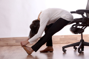 Business woman practices exercises at work place, peaceful woman enjoys stretching on the office chair.