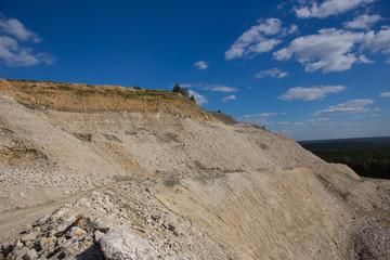 Big heap of mininig feldspar quarry at summer day