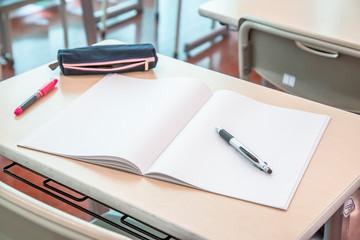 教室に並ぶ机と椅子、机の上のノートとペン。スクールイメージ。