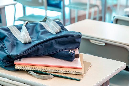 教室に並ぶ机と椅子、スクールバックから飛び出したノートとペンケース。スクールイメージ。