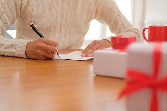 man writing christmas letter greeting card holiday wishes. xmas celebration.