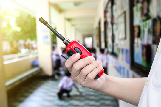A man holding a red radio communication or handheld walkie-talkie at school.