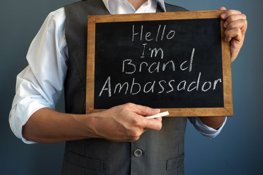 Man is holding blackboard with sign I am Brand Ambassador.