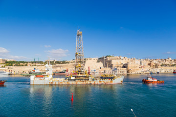 Valletta, Malta. Tugboats move a drilling ship in the Great Bay