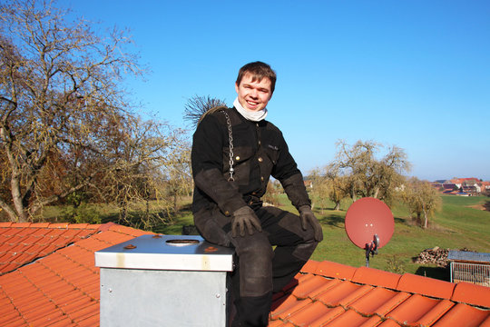 A chimney sweeper sitting on a flue on top of the roof