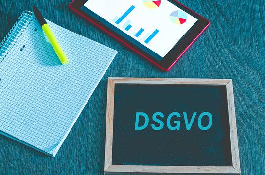 Tafel mit der Aufschrift DSGVO (Datenschutzgrundverordnung) in englisch GDPR (General Data Protection Regulation) mit einem Tablet und Block zur Einführung der DSGVO in der EU